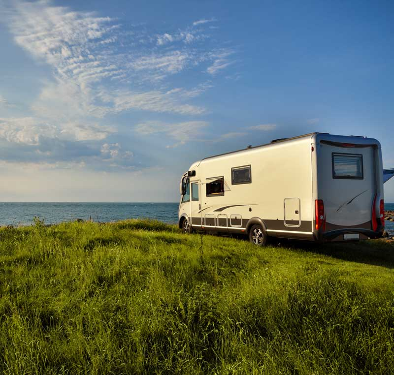 A recreational vehicle parked in front of a lake during sunset