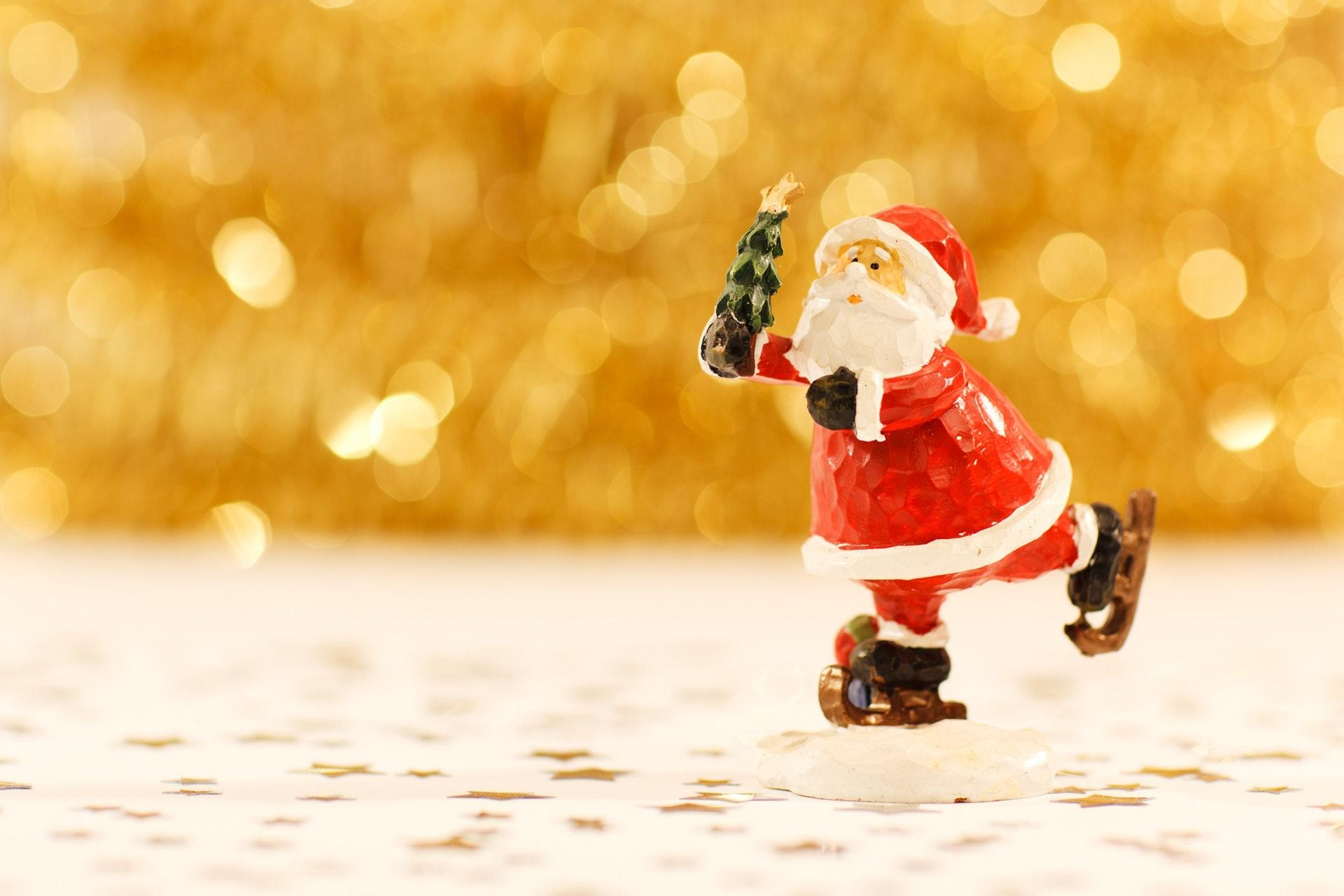 Ice skating Santa toy holding little Christmas tree